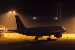 Passenger airplane waiting on an aiport at night. A passenger airplane waiting on an aiport at night Royalty Free Stock Image
