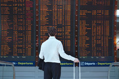 Passenger in airport. Passenger looking at timetable board at the airport Royalty Free Stock Image