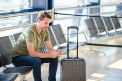 Passenger in a airport lounge waiting for flight aircraft. Young man with cellphone in airport waiting for landing. Passenger in an airport lounge waiting for Royalty Free Stock Images