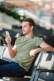 Passenger in a airport lounge waiting for flight aircraft. Young man with cellphone in airport waiting for landing. Passenger in an airport lounge waiting for Stock Photo