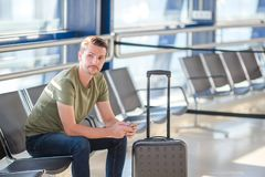 Passenger in a airport lounge waiting for flight aircraft. Young man with cellphone in airport waiting for landing. Man passenger in an airport lounge waiting Royalty Free Stock Images