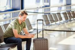 Passenger in a airport lounge waiting for flight aircraft. Young man with cellphone in airport waiting for landing. Young man with smartphone in an airport Stock Images