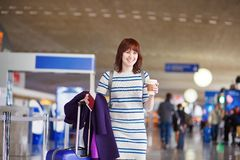 Passenger at the airport with take away coffee. Beautiful young female passenger at the airport with take away coffee Stock Photos