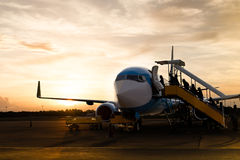 Passenger boarding on airplane in vacation in silhouette. At sunset time Stock Photos
