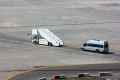 Passenger boarding steps and minibus on the airport apro. Passenger boarding steps vehicle and minibus on the airport apron Royalty Free Stock Photos