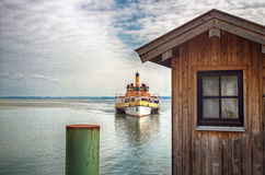 Passenger boat approaching a pier in Chiemsee lake, Bavaria, Germany Royalty Free Stock Photography