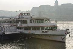 Passenger boat on the Buda Castle background on the Danube River in Budapest, Hungary - Backlight photo.  stock photo