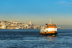 Passenger boat (Cacilheiro) crossing the Tagus River with the Lisbon skyline as background Royalty Free Stock Photography
