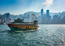 Passenger boat carrying tourists between the Islands of Hong Kong skyscrapers in the background royalty free stock image