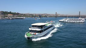 A passenger boat crossing below the Galata Bridge in Istanbul Turkey. Istanbul, Turkey - May 25, 2013: A passenger boat crossing below the Galata Bridge. Slow stock footage