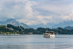 Passenger boat in front of snow covered Alps mountains peaks in Stock Image