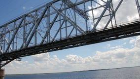 A passenger boat passes under the railway bridge on the Volga river near Saratov, Russia.  stock video