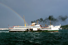 Passenger boat with rainbow. A classic steamboat on Bosporus seen from above Royalty Free Stock Photo