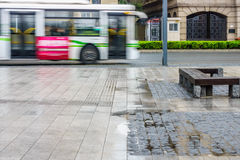 A passenger bus on road in city after rainy day Royalty Free Stock Photography