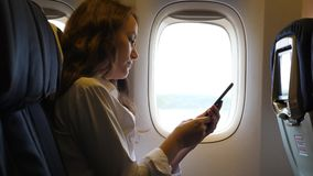 Businesswoman using smartphone in airliner. Passenger businesswoman using smartphone in airliner, sitting alone near window stock video footage