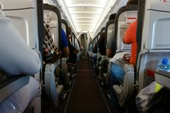 Passenger cabin in flight with people. Economy class. View from the path between rows of aircraft . Stock Image