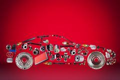 Passenger car assembled from new spare auto parts for shop aftermarket. Isolated on red background Royalty Free Stock Photography