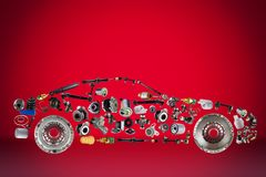 Passenger car assembled from new spare auto parts for shop aftermarket. On red background Stock Photos