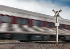 Passenger Car Flies by Railroad Crossing Stock Photo