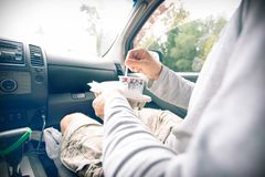 Passenger in the car holding cardboard tray with a cup of coffee Stock Photography