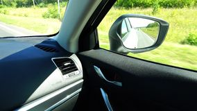 The passenger in the car looks in the side rearview mirror.  stock video