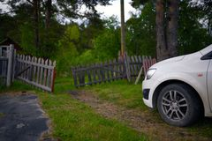 Passenger car on rural yard about old wooden gate Stock Image
