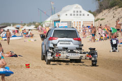 Passenger car with a trailer, riding on the beach with holidaymakers Stock Images