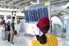Passenger checking flight status at airport information display, Asian traveler looking at departure and arrival board. stock photos