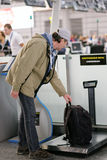 Passenger checking the weight of his luggage Royalty Free Stock Image