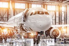 Passenger commercial airplane on maintenance of engine turbo jet and fuselage repair in airport hangar. Aircraft with open hood on. The nose and engines, as stock images