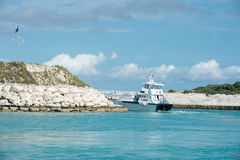 Passenger cruise ship in sea leaving bay with rocky coast Stock Images