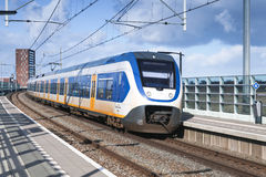 Passenger electric train goes near railway platform. In Amsterdam, Netherlands Royalty Free Stock Photos