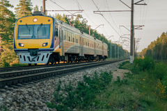 Passenger electric train. Moving through forest in Riga Stock Photo