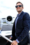 Passenger embarking. Young man embarking business jet with the engine in the background stock image