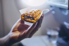 Passenger enjoying snack in airplane. Traveling by airplane. Passenger enjoying snack in economy class during flight stock photos