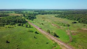 Passenger express train rides through the countryside. In summer. Aerial view stock video