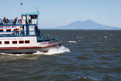 Passenger Ferry crossing lake to Ometepe Island where you can see Conception volcano rising in the background Royalty Free Stock Image