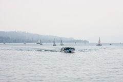 Passenger ferry on a lake with sailboats Royalty Free Stock Photography
