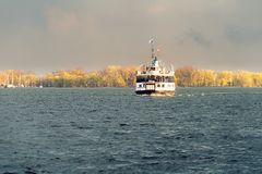 A passenger ferry sails across Toronto harbour at sunset royalty free stock images