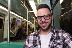 Passenger guy wearing glasses in public transport. Concept of commute, public transportation, mobility royalty free stock images