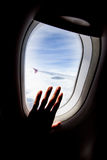 Passenger hand touch window of airplane Royalty Free Stock Image
