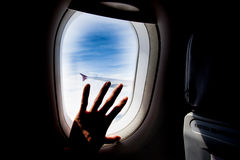 Passenger hand touch window of airplane Royalty Free Stock Photography