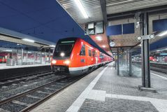 Passenger high speed train on the railway station at night in Europe. Urban landscape with modern commuter train on the railway platform with illumination royalty free stock photography