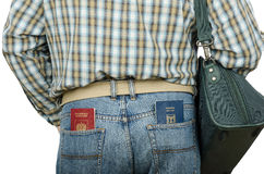 Passenger holding Russian and Israeli passports in rear pockets. Passenger in blue jeans holding Russian and Israeli passports in his rear pockets Stock Photos