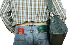 Passenger holding Tonga and Russian passports in rear pockets. Passenger in blue jeans holding Tonga and Russian passports in his rear pockets Royalty Free Stock Photos