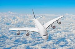 Passenger huge liner airplane fly above clouds and blue sky. royalty free stock image