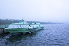 Passenger hydrofoil boat on the docks of Onego lake in foggy weather. Royalty Free Stock Photography