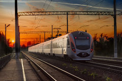 Passenger inter-city train in city on the sunset background Stock Photos