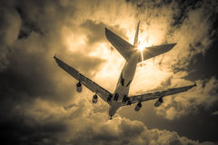 Passenger jet. Abstract of a large passenger jet landing through golden clouds Royalty Free Stock Image