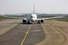 Passenger Jet Aircraft Taxiing on Airport Runway. Commercial passenger jet aircraft taxiing on an airport runway before take off or after landing Royalty Free Stock Photos
